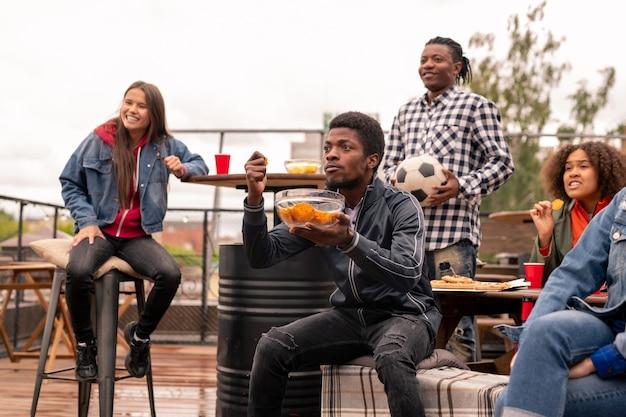 Jovem tenso de etnia africana com uma tigela de batatas fritas e seus amigos assistindo à transmissão do jogo