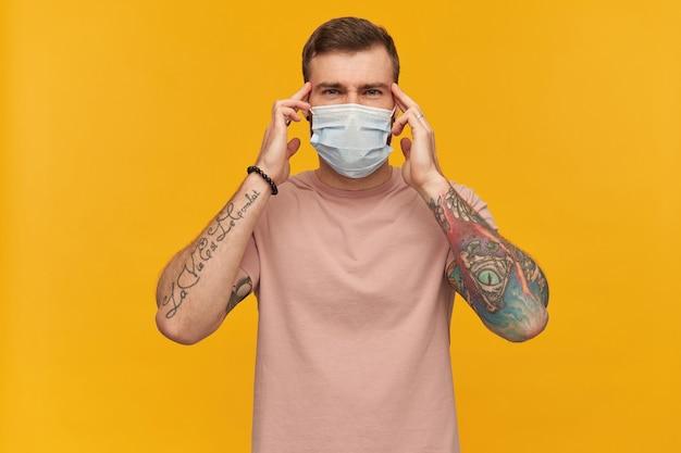 Jovem tenso e tatuado homem barbudo com camiseta rosa e máscara higiênica para evitar infecção tocando suas têmporas com as duas mãos e tendo dor de cabeça sobre a parede amarela