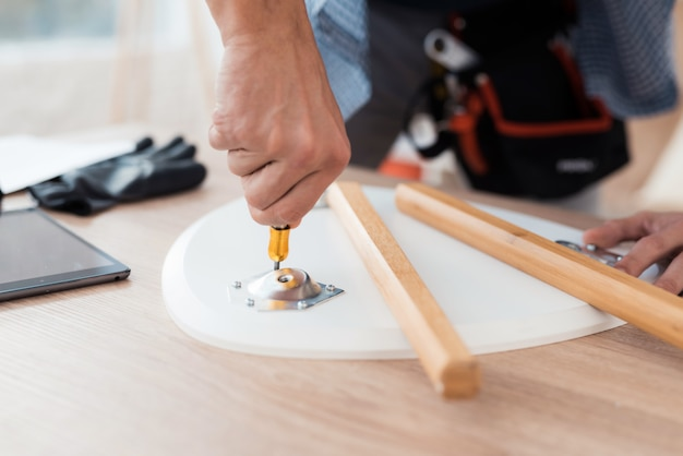 Jovem tenta se dobrar sua mesa de café e fezes.