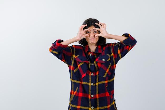 Jovem tentando abrir os olhos com os dedos em uma camisa quadriculada e parecendo uma fofa. vista frontal.