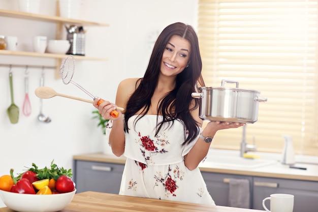 Jovem tentando cozinhar algo na cozinha