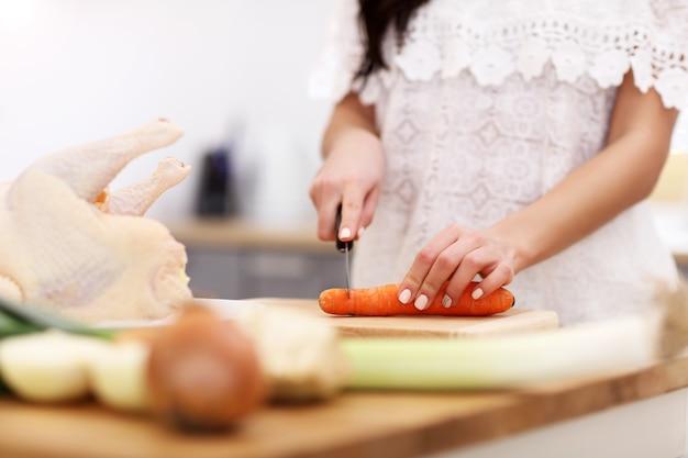 Jovem tentando preparar canja de galinha na cozinha