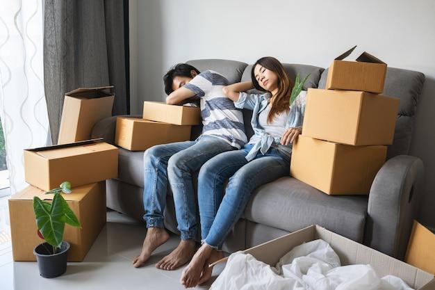 Jovem tentou casal movendo-se em nova casa, sentado e relaxando no sofá com caixas de papelão