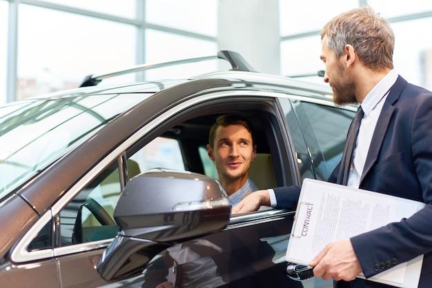 Jovem, testando o carro novo na sala de exposições
