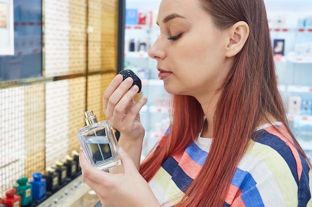 Jovem testando uma amostra de perfume em loja de maquiagem