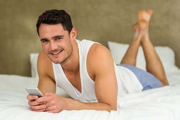 Jovem, texting, sorrindo, enquanto, mentindo cama, com, seu, telefone