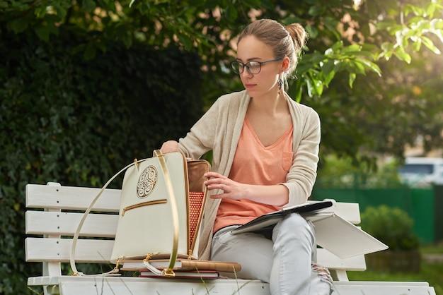 Jovem tira algo de sua bolsa branca com zíper no parque de bancos de madeira branca no parque verde da cidade. ela usa calça jeans, cardigã, óculos.