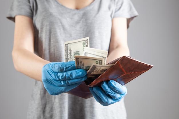 Jovem tira dinheiro da carteira com luvas