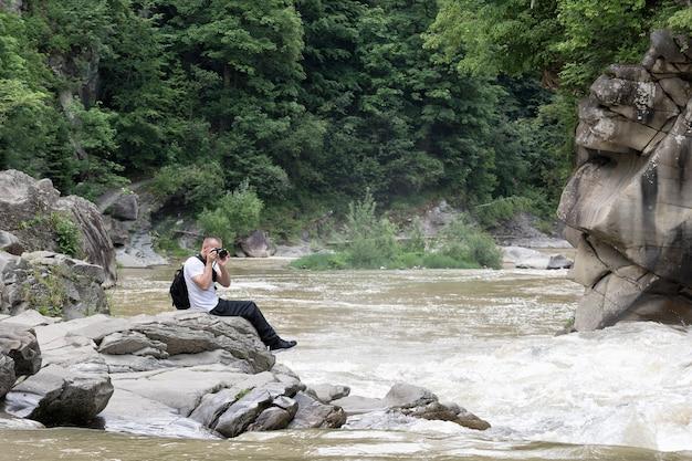 Jovem tira fotos na margem de um rio tempestuoso. dia ensolarado de verão