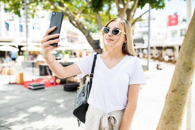 Jovem tira selfie de mãos com telefone na rua da cidade de verão.