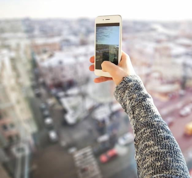Jovem tira uma foto de uma cidade do edifício alto