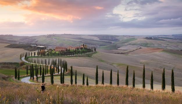 Jovem tira uma foto de uma fazenda e uma estrada com ciprestes ao pôr do sol em val dorcia toscana itália