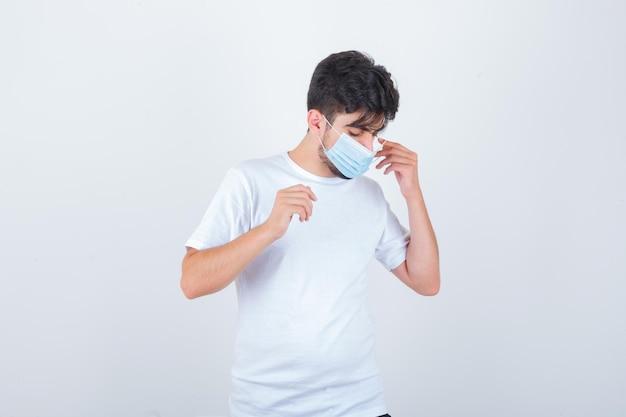 Jovem tirando a máscara médica de camiseta branca e parecendo pensativo