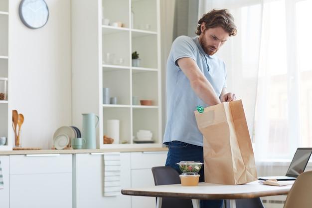 Jovem tirando as caixas com comida do saco de papel na cozinha ele recebe entrega de comida