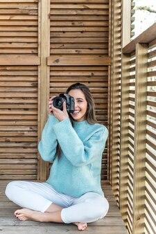 Jovem tirando foto com a câmera do terraço