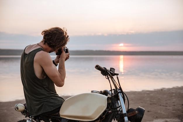 Jovem tirando fotos com a câmera enquanto está sentado em sua moto ao ar livre