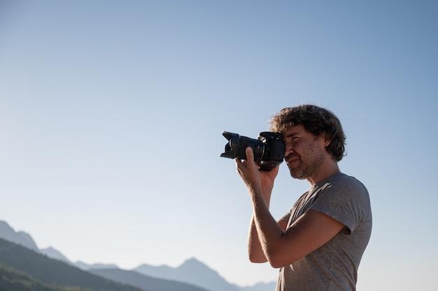 Jovem tirando fotos com uma câmera profissional dslr lá fora em uma linda manhã de verão.