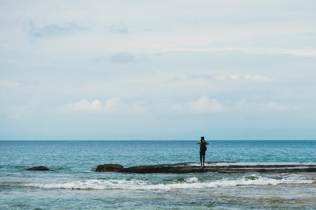 Jovem tirando fotos do mar parado na costa. horizonte. mar azul e céu azul com nuvens.