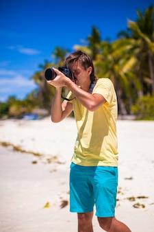 Jovem tirando fotos em uma praia tropical