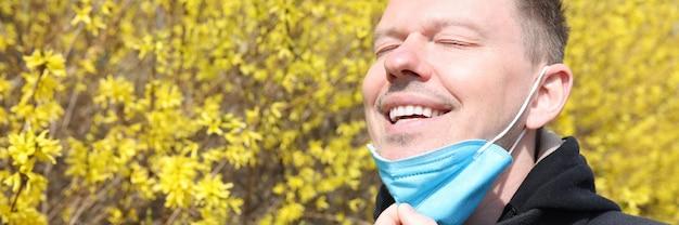 Jovem tirando o respirador protetor do rosto perto de uma árvore florida