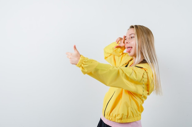 Jovem tirando selfie com a mão na camiseta, jaqueta e parecendo engraçada