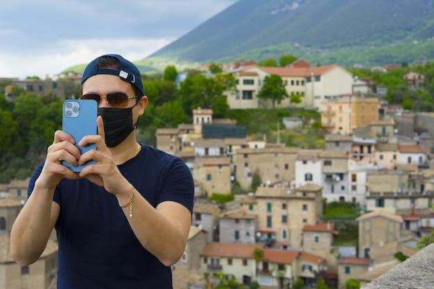 Jovem tirando uma foto com o iphone 12 pro max em cidade italiana