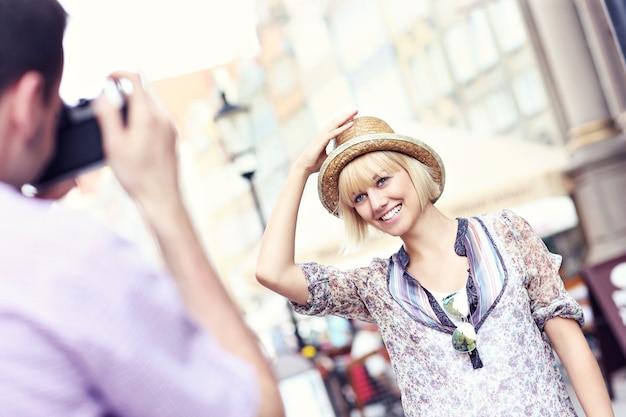 Jovem tirando uma foto da namorada enquanto viaja por gdansk, na polônia