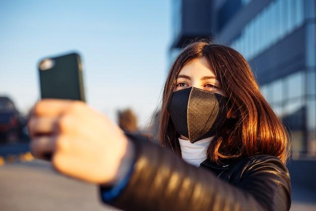 Jovem tirando uma foto de selfie com uma máscara médica preta perto de um shopping temporário fechado devido à quarentena de epidemia mundial