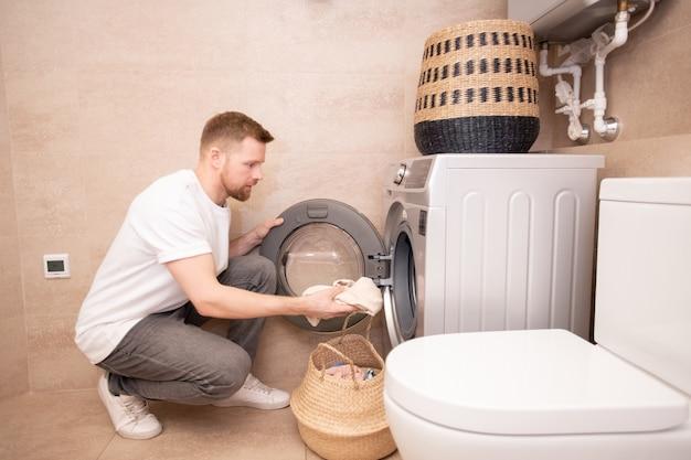 Jovem tirando uma toalha suja da cesta e colocando-a na máquina de lavar enquanto se agacha contra a parede do banheiro