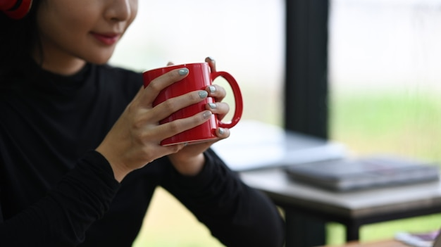Jovem tiro recortado segurando a xícara vermelha de café quente.