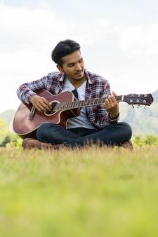 Jovem toca guitarra enquanto está sentado na grama verde contra a natureza e a paisagem de montanha
