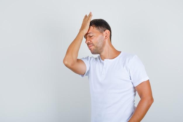 Jovem tocando a testa com a palma da mão em t-shirt branca e parecendo esquecido, vista frontal.