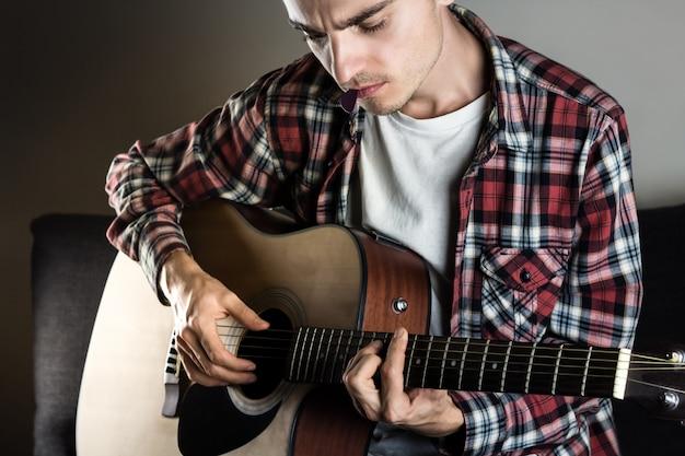 Jovem tocando acorde na guitarra
