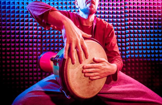 Jovem tocando djembe no estúdio de gravação de som.