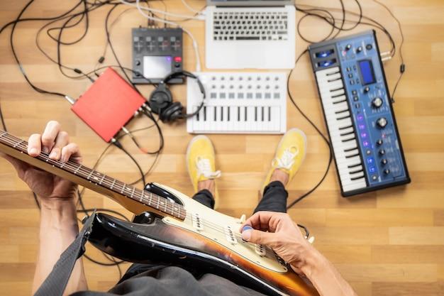 Jovem tocando guitarra elétrica na sala de ensaio, ponto de vista baleado. vista superior do produtor masculino no estúdio caseiro tocando guitarra e instrumentos eletrônicos.