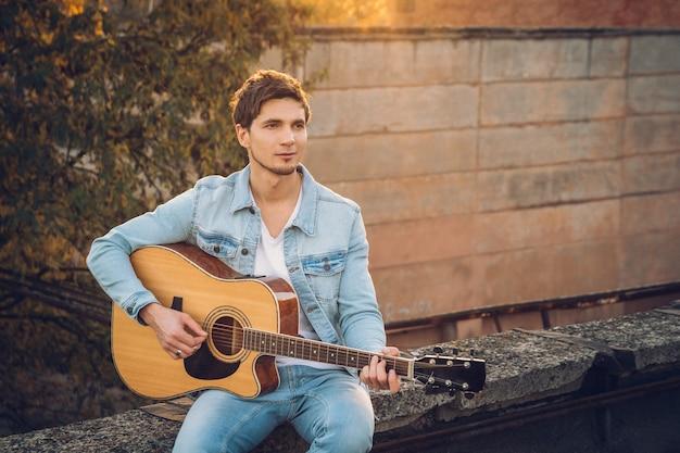 Jovem tocando guitarra na cidade em um fundo de raios de sol