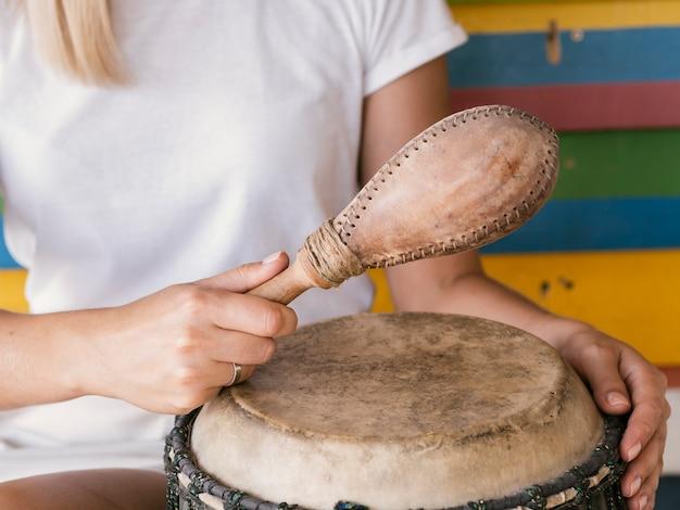 Jovem tocando instrumentos de percussão perto de parede multicolorida