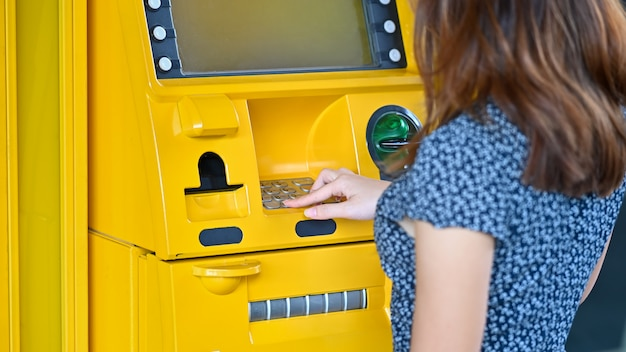 Jovem tocando no caixa eletrônico em um shopping.
