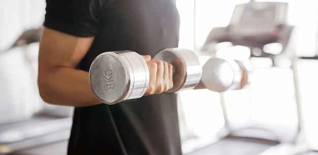 Jovem tocando onda de haltere para a construção de músculo bíceps no ginásio