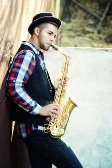 Jovem tocando saxofone do lado de fora perto da velha parede