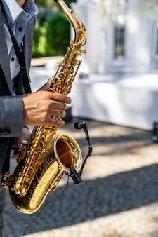 Jovem tocando saxofone no casamento. fundo desfocado. foco seletivo.