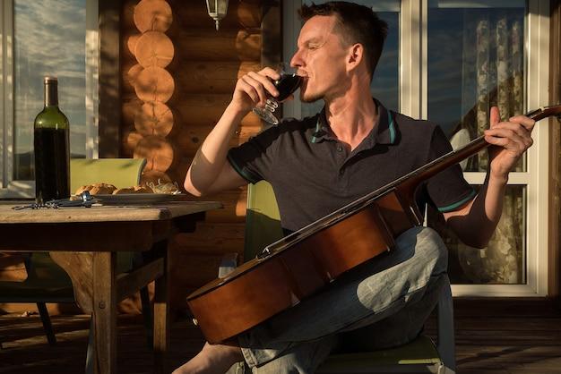 Jovem tocando violão e bebendo vinho sozinho. quarentena do covid19.