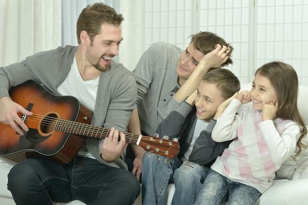Jovem tocando violão para sua família