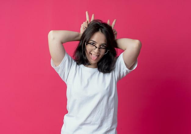 Jovem tola e bonita caucasiana usando óculos fazendo orelhas de coelho, mostrando a língua isolada em um fundo carmesim com espaço de cópia