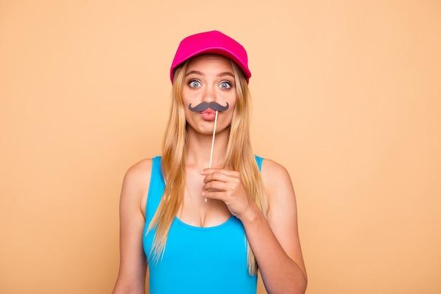Jovem tola segurando bigodes falsos