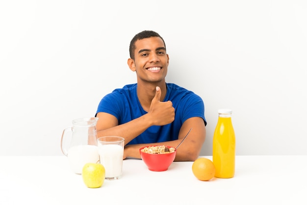 Jovem tomando café da manhã em uma mesa dando um polegar para cima gesto