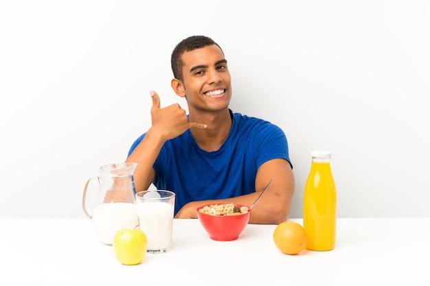 Jovem tomando café da manhã em uma mesa fazendo gesto de telefone