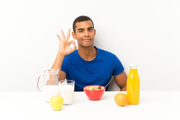 Jovem tomando café da manhã em uma mesa, mostrando um sinal de ok com os dedos