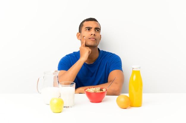 Jovem tomando café da manhã em uma mesa pensando uma idéia