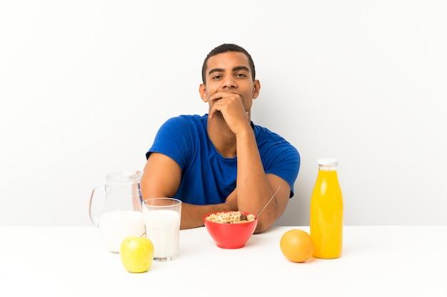 Jovem tomando café da manhã em uma mesa rindo